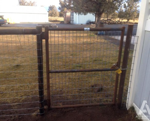Residential fence with iron pipe gate